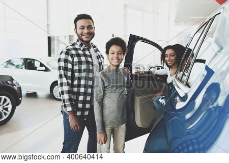 African American Family At Car Dealership. Father, Mother And Son Posing Near New Car.
