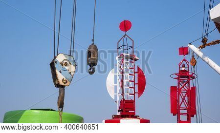 Part Of Crane Hoisting Block, Hook, Steel Wire Rope With Red Fairway Buoy And White Boom Against Blu