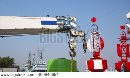 White Crane Boom And Hoisting Block, Hook, Steel Wire Rope With Red Fairway Buoys Against Blue Sky B