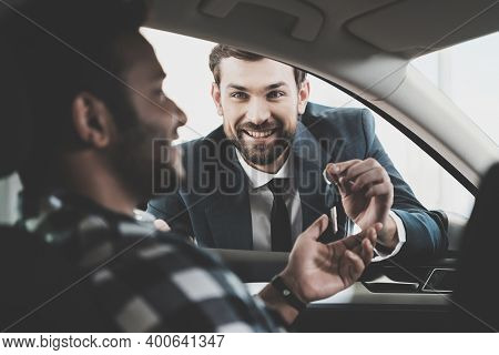 Salesman Is Giving Keys For New Grey Car. Salesman Smiles And Gives The Keys To A New Car To An Afri