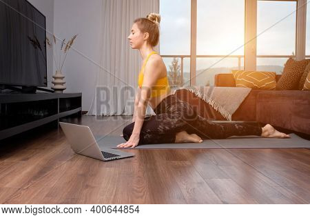 Woman doing online yoga at home. Female teaches asana in video conference. Health care, authenticity, sense of balance and calmness.
