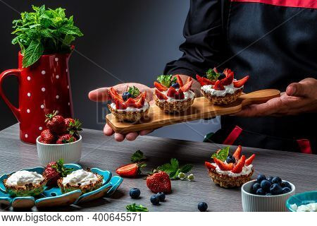 Close Up Master Chef Hands Making A Delicious Strawberry Tarts. Fruit Dessert Tarts With Cheese Crea