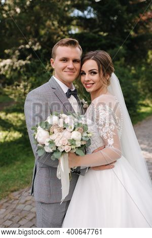 Beautiful Couple Of Groom And Bride On Wedding Day Walking Outdoors. Attractive Young Bride With Han