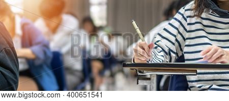 Exam At School With Student's Taking Educational Admission Test In Class, Thinking Hard, Writing Ans