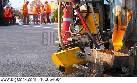 Close Up Thermoplastic Spray Marking Machine With Blurred Background Of Road Workers Team Discussing