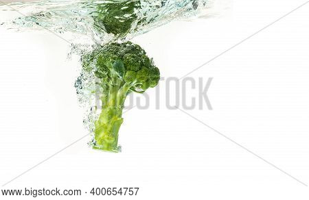 Close-up Of Broccoli Splash Into Water Isolated On White. Healthy Food Concept