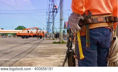 Back Side And Midsection Of Electrician Lineman With Outdoor Electrical Installation Equipment And B