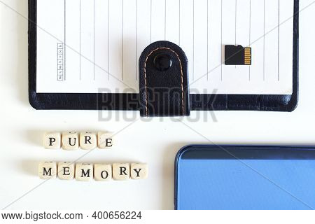 Micro Sd Memory Card With An Open Notebook And A Blue Smartphone Next To The Inscription: Pure Memor