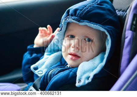 Crying Sad Caucasian Baby Infant Sitting In Car Seat. Adorable Kid In Outwear Clothes In Automobile