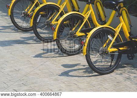 Row Of Yellow Bikes Parked On Cobblestone Pavement In Public Area, Side View With Copy Space