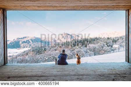 Woman With Thermos Flask Sitting With Her Beagle Dog In The Big Wooden Hangar With A Huge Panoramic