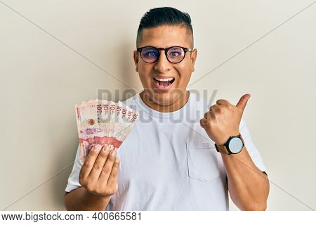 Young latin man holding 10 colombian pesos banknotes pointing thumb up to the side smiling happy with open mouth