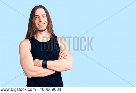 Young adult man with long hair wearing rocker style with black clothes and contact lenses happy face smiling with crossed arms looking at the camera. positive person.
