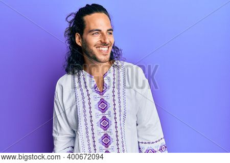 Young handsome man with long hair wearing bohemian and hippie shirt looking away to side with smile on face, natural expression. laughing confident.