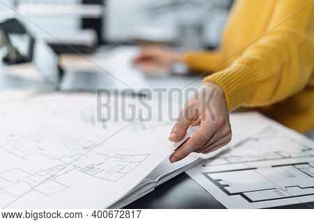 Selective Focus On Woman Hand With Blueprint. Cropped View Of Professional Contractor Working At Off