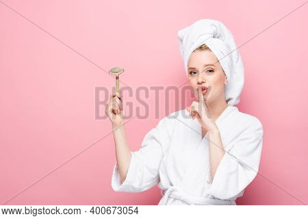 Young Woman In Bathrobe With Towel On Head Holding Jade Roller And Showing Shh Isolated On Pink.