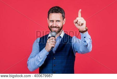 Talk Show Host. Happy Speaker Speak Into Microphone Keeping Finger Raised. Speaker Perform Speech. V