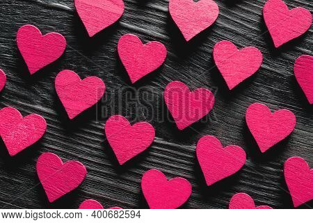 Pattern Of Purple Hearts On Black Wooden Background