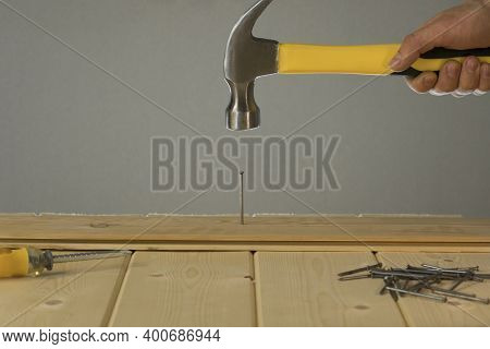 Hammer Hitting Nail On The Head. Diy. Carpenter Hands With Hammer Wood And Nail. Using Hammer On Woo