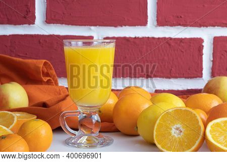 Freshly Squeezed Orange Juice In A Glass Glass, Whole And Squeezed Oranges On The Table, Behind A Br