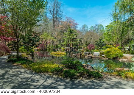 Ball Ground, Georgia/usa-04/11/18  Japanese Garden With Statues And Variety Of Plants And Trees Surr