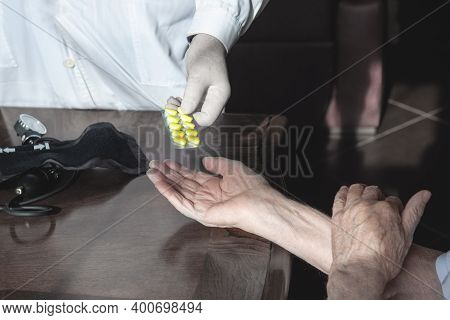 Doctors Hand Gives An Old Patient A Pill. Gerontology Service, Nursing Home. Unrecognizable People,