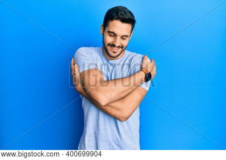 Young hispanic man wearing casual clothes hugging oneself happy and positive, smiling confident. self love and self care