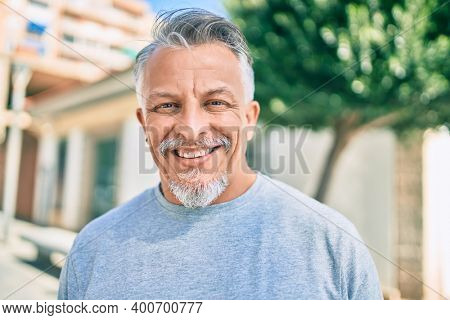 Middle age hispanic grey-haired man smiling happy standing at the city.