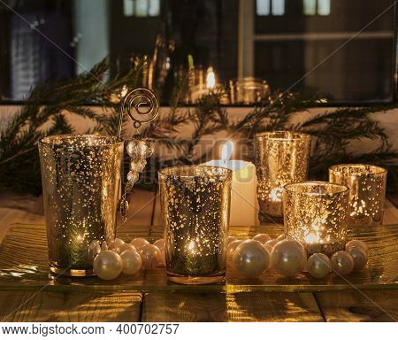 New Years Or Christmas Evening Composition On The Windowsill. Burning Candles, Golden Glass Candlest