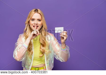 Blonde Young Woman In Colorful Outfit Holding Blank Card And Showing Shh Sign On Purple Background.
