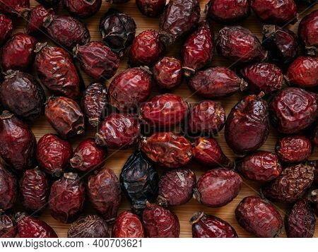 Dried Berries Of Dog Rose Or Rosa Canina. Dry Fruits Of Sweet-brier Or Rose Hips On Wooden Backgroun