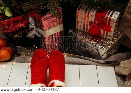 Feet In Christmas Socks. Close Up On Feet. Winter And Christmas Holidays Concept. Cozy Scene. Backgr