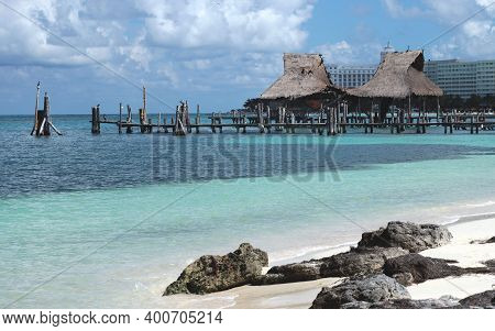Blue Caribbean Sea With White Sands And Piers With Roofed Buildings In The Background. Cancun. Mexic