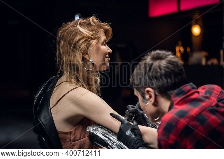A Young Red-haired Girl Came To The Tattoo Artist In The Salon To Make The First Tattoo In Her Life