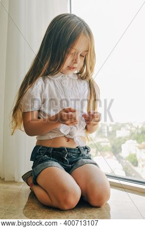 Portrait Of Cheerful Kid Sits At Windowsill. Child In White Shirt And Shorts By The Window At Home
