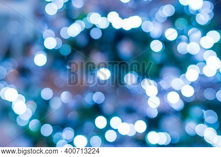 Abstract Blue And White Bokeh Festoon On A Dark Green Background. Bokeh From Cold Light Garland On A