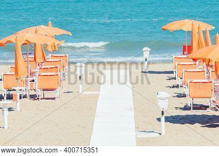 Sunbeds And Parasols On The Seashore. Beach, Sea And Umbrellas On Summer Day. Adriatic Coast, Rimini