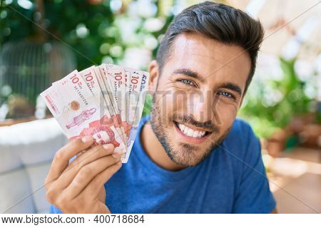 Young hispanic man smiling happy holding colombian pesos banknotes at the terrace.