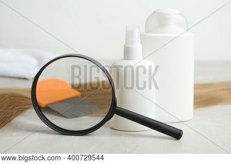 Cosmetic Products, Lice Comb, Magnifying Glass And Strand Of Hair On Light Table