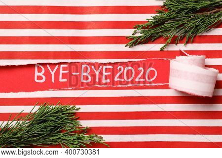 Thuja Branches And Text Bye-bye 2020 On Red Background, View Through Torn Striped Paper