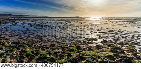 Warm Evening Light Over A Wild Sand And Rock Beach With Tidal Pools And Seagulls Flying
