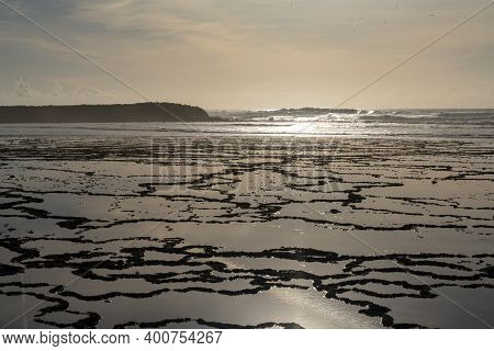 Golden Evening Light Reflectiing In Tidal Pools On A Rocky Beach With The Ocean Behind