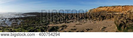 Panorama View Of Golden Evening Light Reflectiing In Tidal Pools On A Rocky Beach With The Ocean Beh