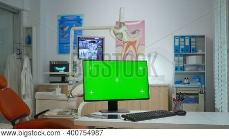 Computer With Green Screen Placed In Front Of Camera In Empty Modern Equipped Stomatological Room. S