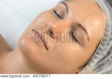 Young Woman In Cosmetology Clinic With Yellow Peeling On Her Face, Closeup Side View Of Face. Cleans