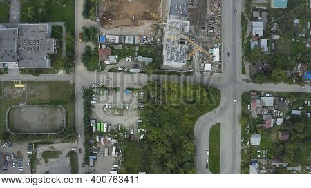 Top View Of Construction Site Of Building Next To Residential Buildings. Stock Footage. Green Courty