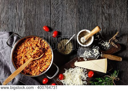 Ground Beef Risotto In A Metal Stewpot With A Spoon On A Dark Wooden Table With Ingredients, Italian