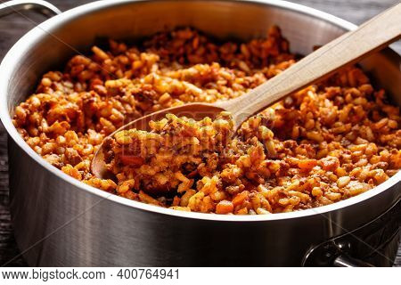 Close-up Of Ground Beef Risotto Bolognese In A Metal Stewpot With A Spoon On A Dark Wooden Table, It
