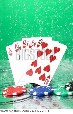Royal Flush Combination Under The Water Drops Against Green Background. Online Gambling. Betting. Ga