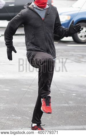 Front View Of A High School Boy Warming Up In A Parking Lot Performing Running Drills Wearing A Gait